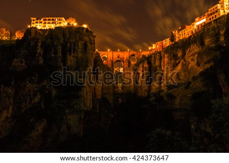 The popular historic landmark of spectacular Puente Nuevo, New Bridge,  illuminated at night, over Guadalevin River in town of Ronda, Andalusia, Spain. - stock photo