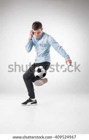 The portrait of fan with ball, holding phone on white background - stock photo