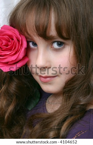 The portrait of the girl of the teenager with red rose on light background. - stock photo