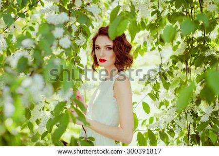 The portrait of this gentle, sensual and sexy brunette girl with bright makeup and red lips, against the background of white flowers and green leaves in the spring - stock photo