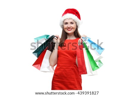 the portrait of young adult beautiful smiling woman wearing on red dress and  Santa Claus hat holding colored shopping bags isolated on white background - stock photo