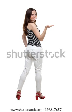 the portrait of young adult smiling woman wearing on white trousers and stripes shirt showing something isolated on white background - stock photo