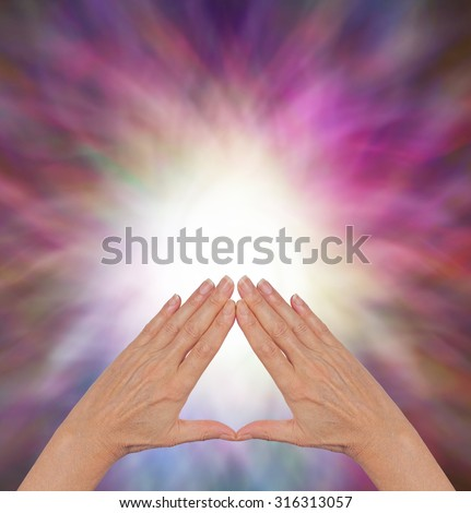 The Power of Pyramid Healing - female hands making a triangle shape on a flowing triangular shaped energy field with plenty of copy space - stock photo