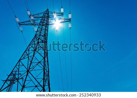 the power pole high-voltage lines with sun and blue sky. energy supply by power line. - stock photo