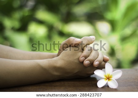 The praying hands on the table - stock photo