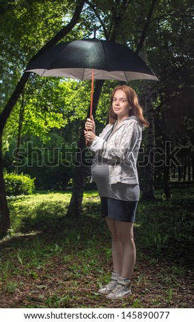 The pregnant woman costs in park under a umbrella - stock photo