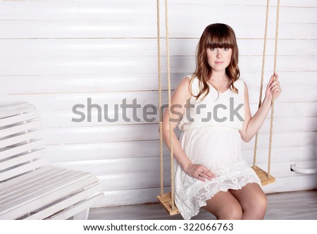 The pregnant woman sits on a swing, white background - stock photo