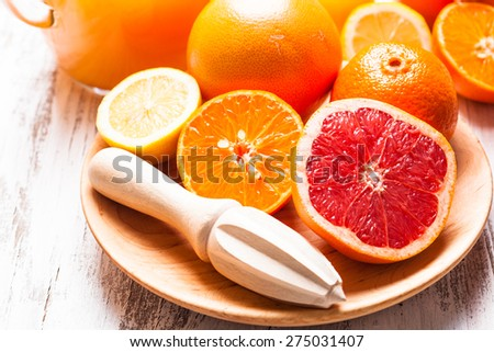The preparation for citrus juice for breakfast. Wooden  citrus reamer with fruits. - stock photo