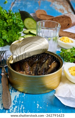 The preserves of sprat in tin Bank on old wooden surface surrounded by other products - stock photo
