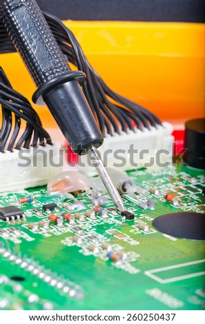 The probe of the digital multimeter on the electronic Board, shallow depth of field - stock photo