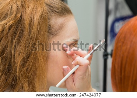The process of applying makeup to the face model. Powder, eye shadow, brush for applying makeup. Master visage working with professional model. - stock photo