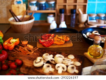 The process of cooking dinner, vegetables and mushrooms housewife cuts to vegetable soup. Mushrooms, peppers, tomatoes, all the vegetables washed and laid out on the table for cutting them to dinner - stock photo