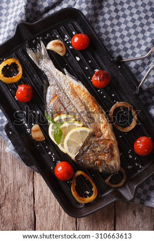 The process of preparing grilled dorado fish on the grill pan on the table. vertical top view - stock photo