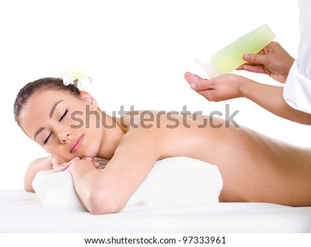 The professional masseur does relaxation massage of back with aromatic oils - white background - stock photo
