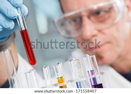 The Professor is examining the red Liquid in a test tube. - stock photo