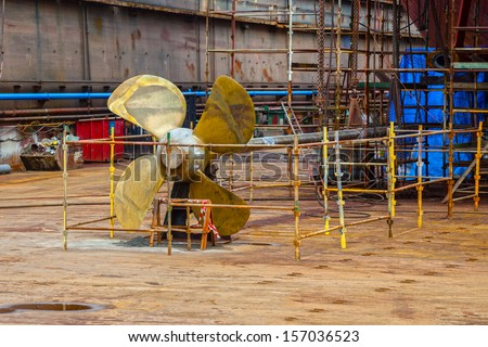 The propeller of a vessel in a dry dock being prepared for maintenance works. - stock photo