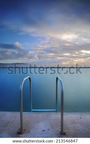 The public ocean rock  pool at Collaroy beach.  Vertical crop.   Collaroy Rock Pool has two odd-shaped  ocean baths with chains,   Note ocean pool, not a private or commercial pool.  - stock photo