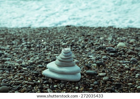 The pyramid of pebbles on the beach. Toned. - stock photo