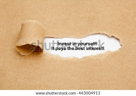 The quote Invest in yourself, it pays the best interest, appearing behind ripped brown paper.  - stock photo