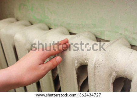 The radiator in the living room. Female hand senses the temperature of the battery.  - stock photo