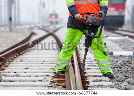 the railroad worker fixes a screw on the rails - stock photo