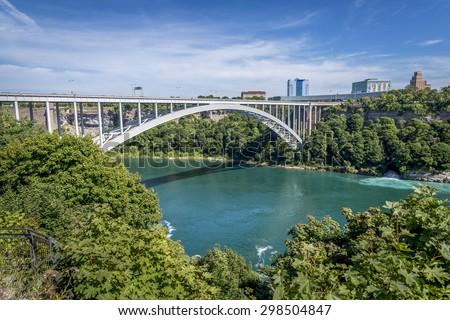 The Rainbow Bridge spans the Niagara River and is a border crossing that joins Niagara Falls Ontario Canada to Niagara Falls New York USA. - stock photo