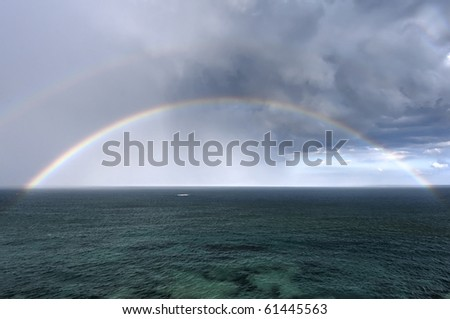 The rainbow over a sea - stock photo