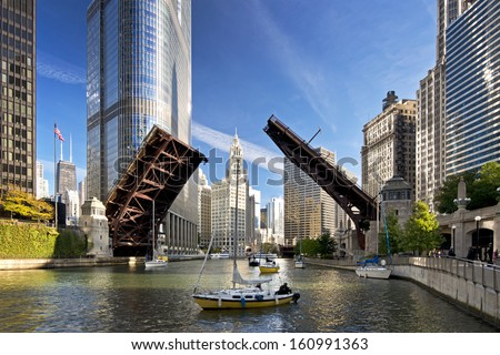 The raising of the bridges on the Chicago River signals the end of another sailing season as sailboats move from their harbor on Lake Michigan to their winter dry dock location. - stock photo