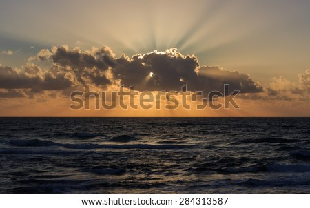 The rays of the setting sun burst out of the cloud - stock photo