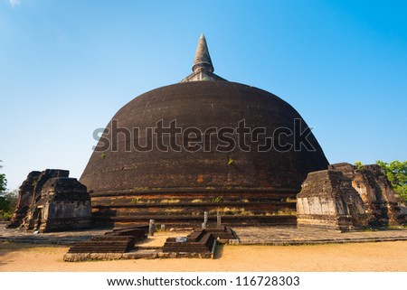 The rear of the Rankoth Vehera, the largest Buddhist stupa at the ruins of the ancient kingdom capitol of Polonnaruwa, Sri Lanka - stock photo