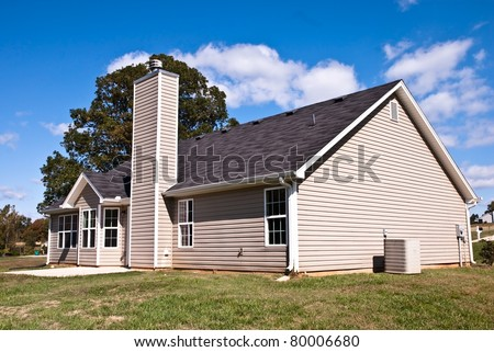 The rear view of a home with slab patio and background of blue sky with clouds. - stock photo