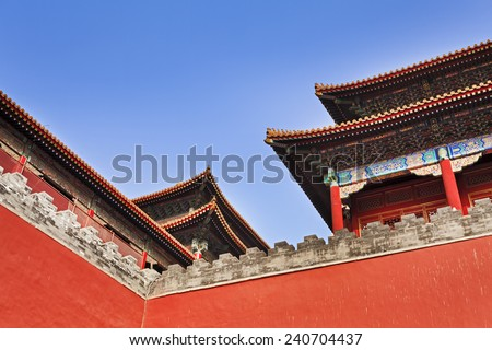 The red and decorated roof tops of Forbidden city imperial palace in Beijing, China, above fortification walls as part of complex temple buildings - stock photo