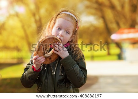 The red and hungry girl greedy bites in park a round bagel with poppy - stock photo