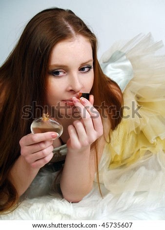 The red beautiful girl with long hair inhales a perfume aroma - stock photo