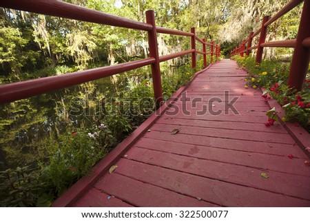 The red bridge in Magnolia Gardens in Charleston is a popular landmark - stock photo