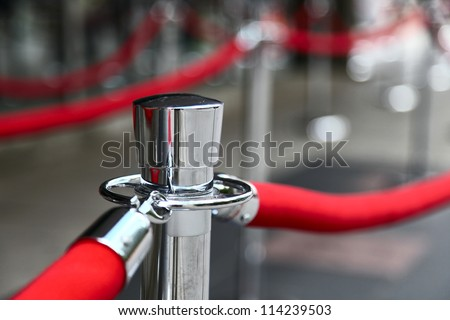 The Red Carpet fence pole with attached red ropes. Closeup, shallow focus. - stock photo