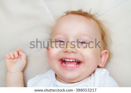 The red-haired and blue-eyed boy laughing - stock photo