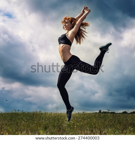 The red-haired girl is engaged in sports exercises on the field under the clouds in an unexpected ray of sunshine - stock photo