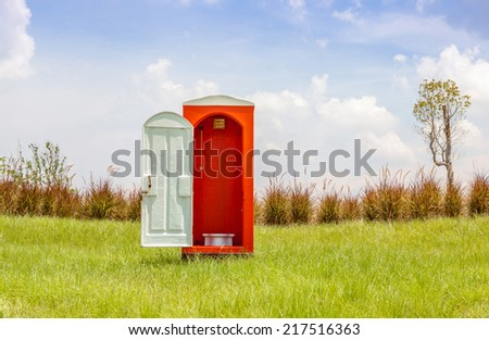 The red toilet with white door open contrast with green grass and tree in the meadow and clear blue sky. - stock photo