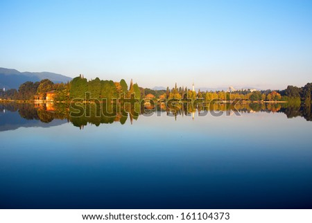 The reflection of forest, pagoda and hut - stock photo