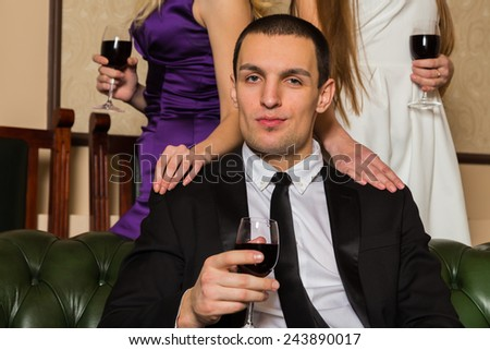 The relationship between a man and a woman - a love triangle, jealousy, betrayal, love. Guy and  girls sitting in the same room on a green couch. Jealous looks awkward situation, betrayal. - stock photo