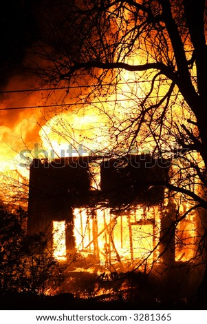 The remaining frame of a house on fire at night - stock photo