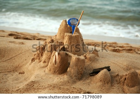 the remains of a childs sand castle on the beach of maui right before the tide washes it away - stock photo