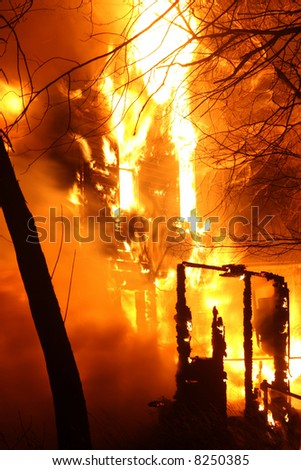 The remains of a house engulfed in flames - stock photo