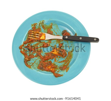 The remains of a plate of ravioli with fork on a blue plate. - stock photo