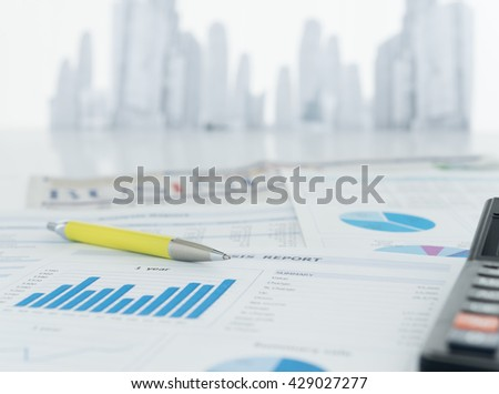 The report analyzes the growing business ,pen, calculator, newspaper on desk of financial adviser with city in background.  - stock photo