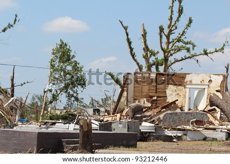 The resiilience of nature is on display as trees sprout leaves on badly damaged limbs in an attempt to recover from damage caused by the direct impact of an EF-5 tornado with winds over 200+ mph. - stock photo