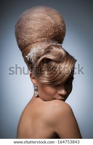 The retro photo of a cute girl with a beautiful vintage hairstyle, stylish topknot and a charming look. - stock photo