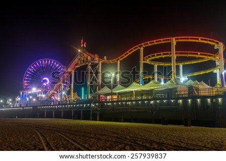 The rides and ferris wheel at the Santa Monica Pier in California at night.  - stock photo