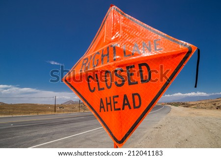 """The """"Right Lane Closed Ahead"""" sign on the side of the road. - stock photo"""